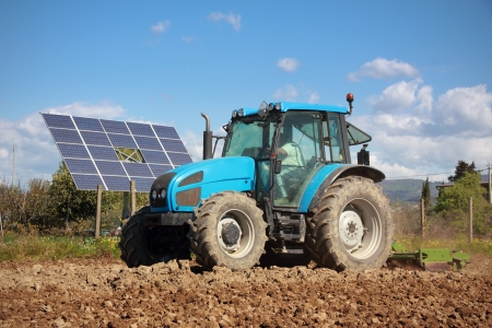 agriculture, tractor working on a field with photovoltaic solar panel in background photo