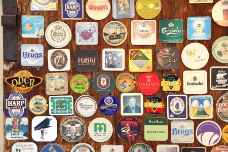 AREZZO, ITALY - CIRCA AUGUST 2011: many different beer coaster on entrance door of old typical pub on august 2011.