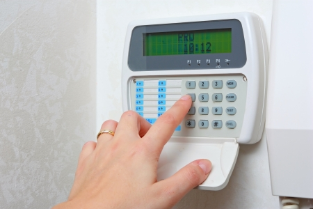 home security system: female hand arming a burglar alarm system