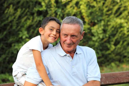 grandsons: grandson smiling with grandfather in a park Stock Photo