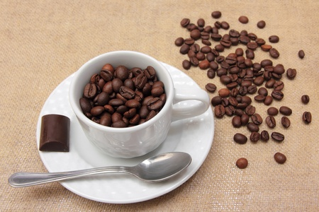 Coffee cup and beans with chocolate and spoon photo
