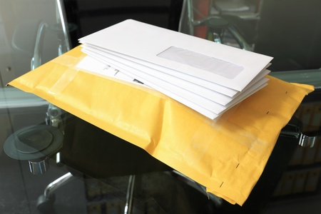 junk mail: pile of paper mails over parcel post in office