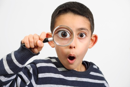 lupa: legrační kluk hledá přes zvětšovací sklo s překvapením Reklamní fotografie