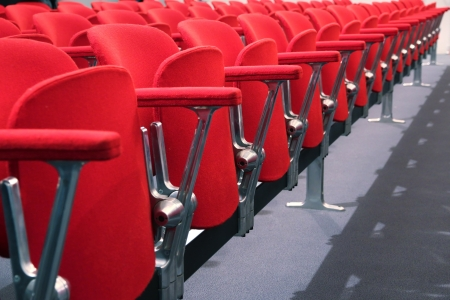 row of red chair seats in an empty conference room auditorium photo