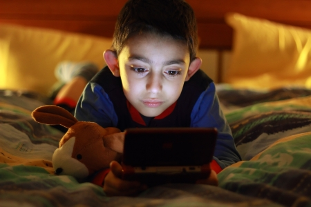 kid in bed wih videogame console  Stock Photo