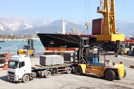 international trade: forklift and truck  in harbor loading cargo ship