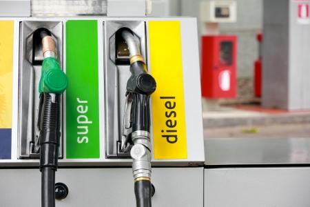 surtidor de gasolina: Boquillas de la bomba en la estación de gas