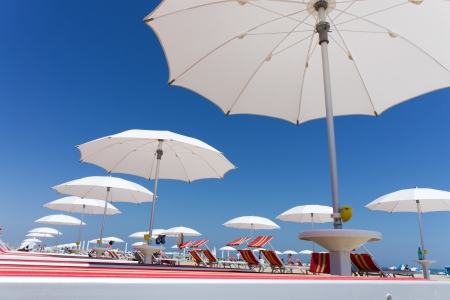 many white beach umbrellas and chairs on Rimini beach, Italy photo