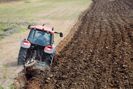 plough machine: agriculture, tractor with plough ploughing a soil field Stock Photo