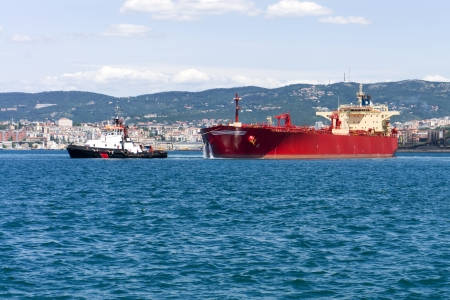 commercial cargo ship heading for port by tug boat photo