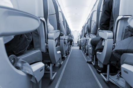 aisle: Interior of airplane with passengers on seats
