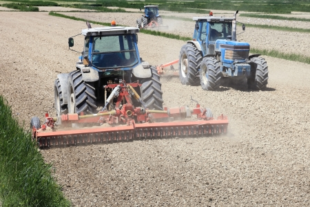 agriculture industrial: Three tractors plowing and farming in the field Stock Photo