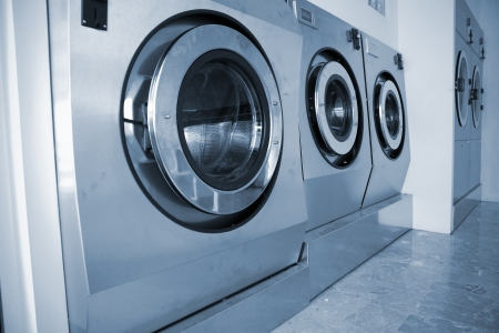 detergents: A row of industrial washing machines in a public laundry