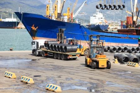 camion grua: camiones, montacargas y barco en el puerto