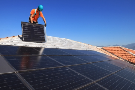 Man during intallation of alternative energy photovoltaic solar panels on roof photo