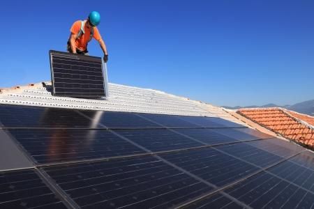 solar array: Man during intallation of alternative energy photovoltaic solar panels on roof