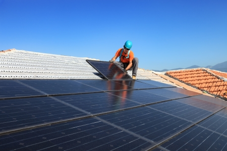 roofer: Man during intallation of alternative energy photovoltaic solar panels on roof