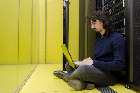 Man sitting on datacenter floor with laptop in front of servers photo