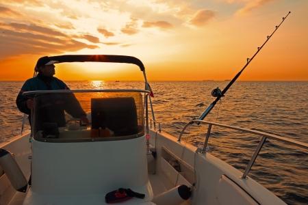 hengelsport: Vissersboot en visser in oceaan bij zonsopgang Stockfoto