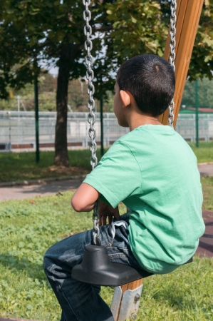 shy: alone kid on a swing in a park