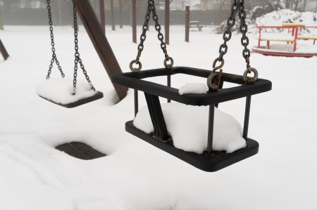 Empty swing with snow in winter on playground  photo