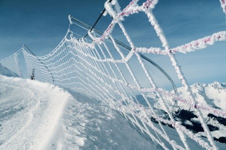 run down: frozen and snow covered protective net on skiing track, italian alps Stock Photo