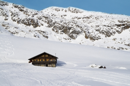 alpine landscape: rustic chalet in snow covered mountains.