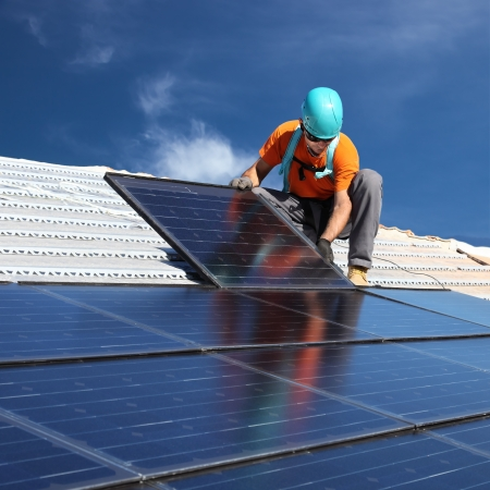 energy work: installing alternative energy photovoltaic solar panels on roof