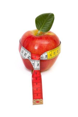 buena salud: manzana roja con cinta métrica corbata en el fondo blanco