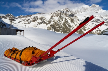 Empty mountain rescue sled over snow on mountain Stock Photo