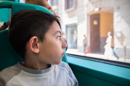 little boy looking through the school bus window photo