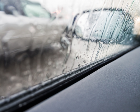 Regen op een auto spiegel en raam Stockfoto