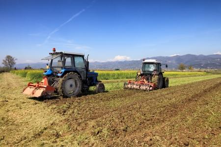 arando: Concepto de la agricultura, tractores arando un campo Foto de archivo