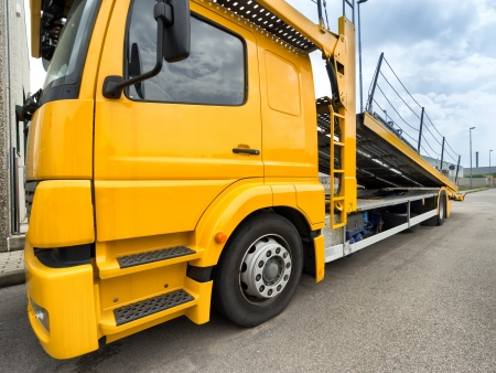 yellow car carrier truck with raised ramp 스톡 콘텐츠