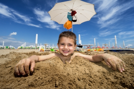 happy kid covered with sand on the beach in summer photo