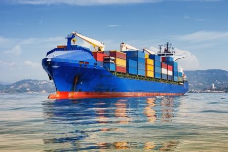 blauwe lading container schip voor anker in de haven Stockfoto