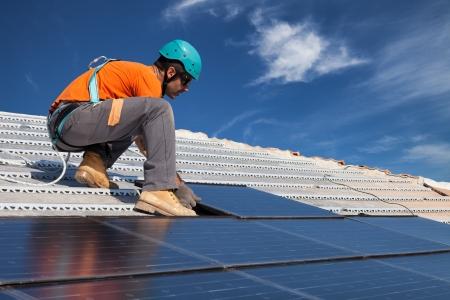 技術者の屋根の上の新世代太陽光発電太陽電池パネルのインストールします。