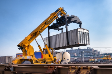 Crane lifting up container in railroad yard