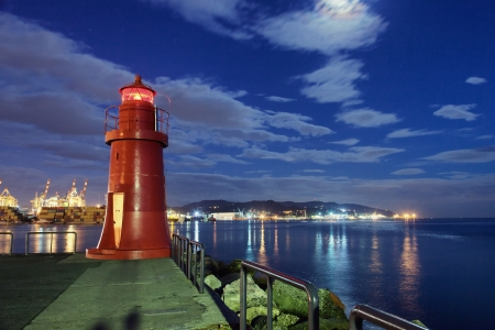 tower house: red lighthouse by night in harbor Stock Photo