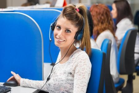 コール センターの電話演算子をサポートして幸せな陽気な笑顔 写真素材