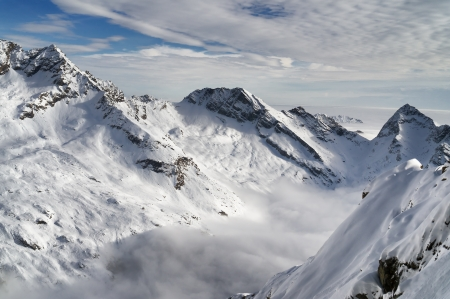 snowscape: Aerial view of snow-covered mountains under cloudy blue sky