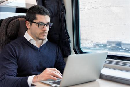 電車の中でラップトップ コンピューターに取り組んで若い男