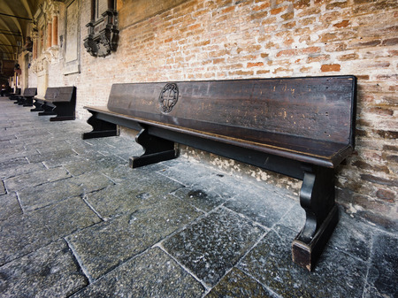 congregation: wooden bench in old church courtyard Stock Photo