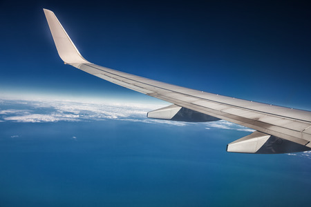 airplane wing in the sky and the horizon over the ocean photo