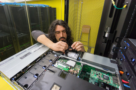young engeneer professional technician repairing server in computer room photo