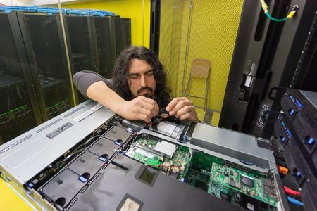 young engeneer professional technician repairing server in computer room photo