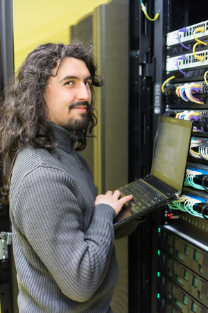 young engeneer professional technician with modern laptop in computer server room photo