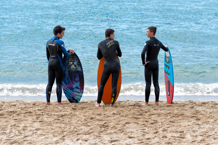 surfers: Cannes, France - APRIL 27, 2014: four young surfers waiting the right wave on the beach. Editorial