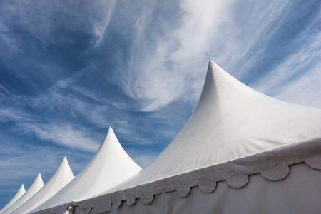 row of white event and party tents against blue sky photo