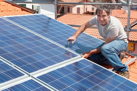 installer: Man installing alternative energy photovoltaic solar panels on roof